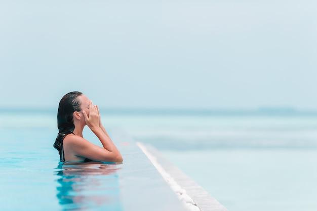 Mulher bonita nova que aprecia a piscina quieta luxuoso