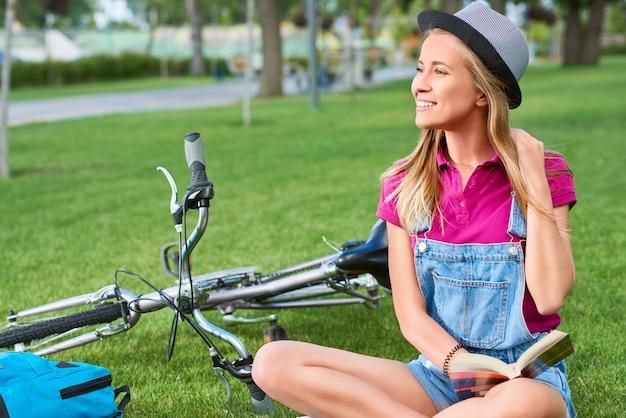 Mulher bonita nova que aprecia lendo um livro após dar um ciclo no positivity de viagem das emoções femininas inteligentes da juventude do turista do estilo de vida ativo do copyspace local do parque que relaxa o conceito.