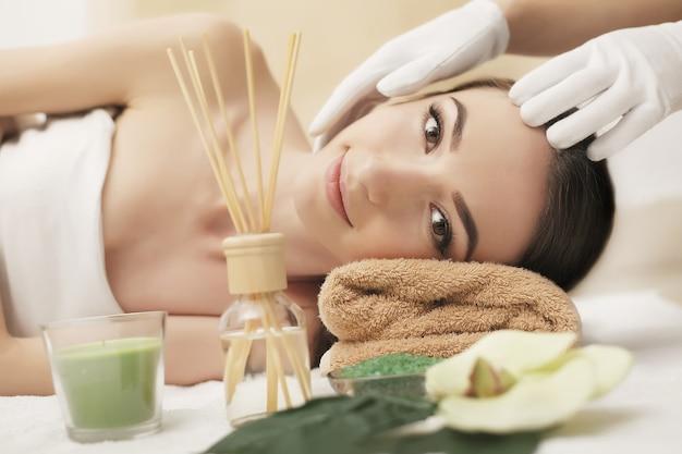 Mulher bonita nova que aprecia o procedimento da massagem de cara