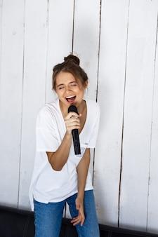 Mulher bonita nova que canta no microfone no sofá em casa.