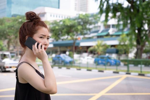 Mulher bonita nova que chama o táxi público pelo telefone em singapura. de pé ao lado da estrada