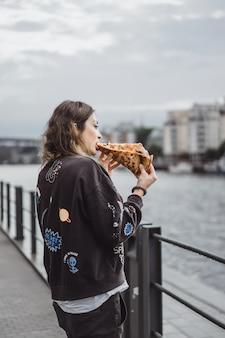 Mulher bonita nova que come uma fatia de pizza na rua da cidade