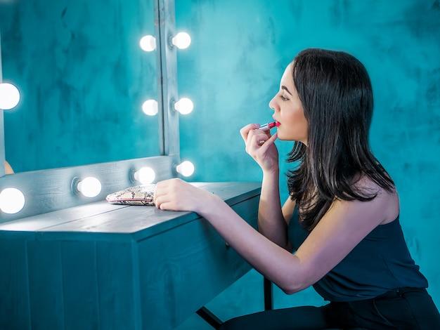 Mulher bonita nova que faz a composição na frente do espelho. garota pintando os lábios dela.