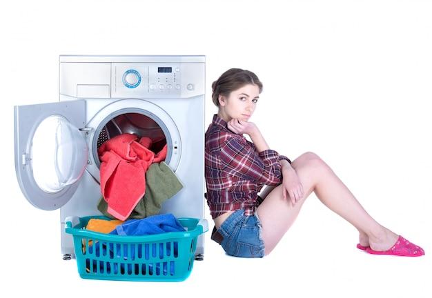 Mulher bonita nova que faz a lavanderia na máquina de lavar.