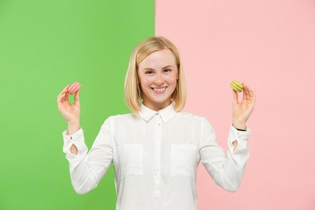 Mulher bonita nova que guarda a pastelaria dos bolinhos de amêndoa em suas mãos, sobre na moda colorido no estúdio.