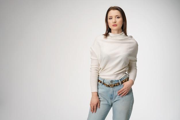 Mulher bonita nova que levanta nas calças de brim no fundo branco
