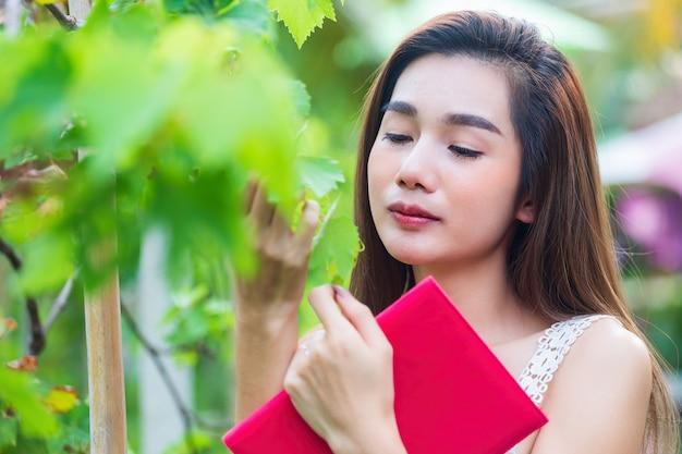 Mulher bonita nova que olha a árvore de uva com felicidade