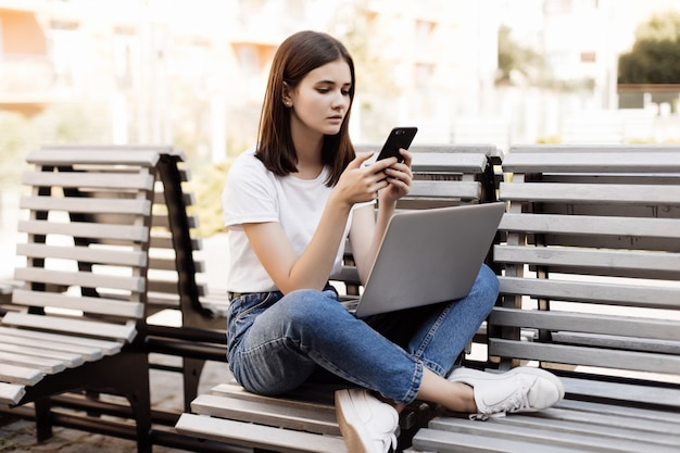 Mulher bonita nova que senta-se no banco no parque verde no dia de verão e que lê a mensagem de texto no telefone celular ao usar o portátil de prata.