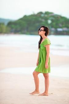 Mulher bonita nova que tem o divertimento no litoral tropical. garota feliz andando na praia tropical de areia branca