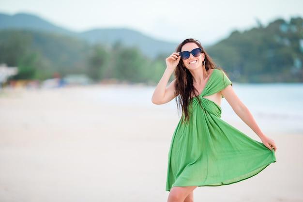 Mulher bonita nova que tem o divertimento no litoral tropical.