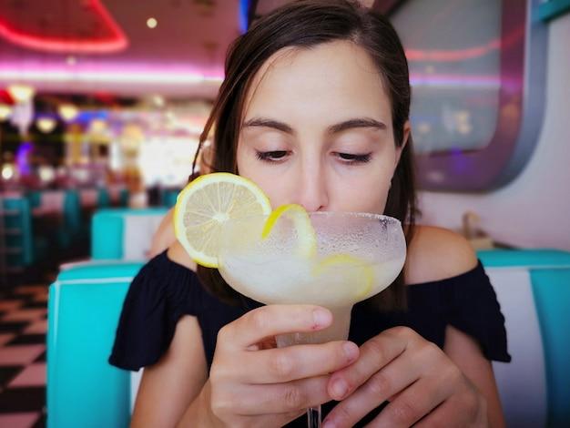 Mulher bonita nova que tem um cocktail em um restaurante