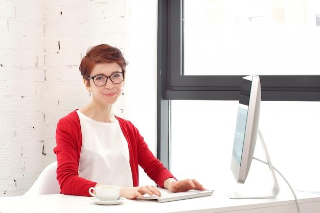 Mulher bonita nova que usa um computador portátil em casa.