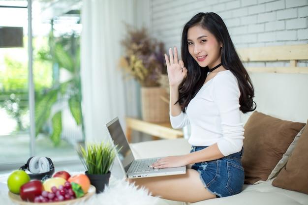 Mulher bonita nova que usa um laptop em casa.