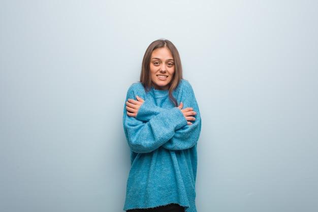 Mulher bonita nova vestindo uma camisola azul vai frio devido a baixa temperatura