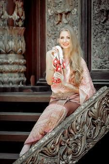 Mulher bonita ocidental no vestido tailandês