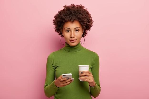 Mulher bonita olha diretamente para a câmera com expressão confiante, segura o celular, vê fotos em redes sociais, bebe café para viagem