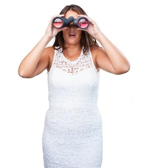 Mulher bonita olhando através de binóculos