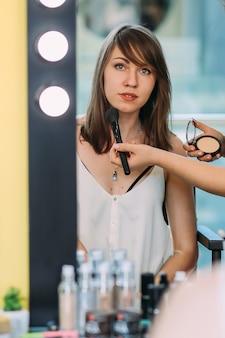 Mulher bonita olhando no espelho de maquiagem com luzes de bulbo. mãos de maquiagem artista aplicando o pó com pincel de maquiagem