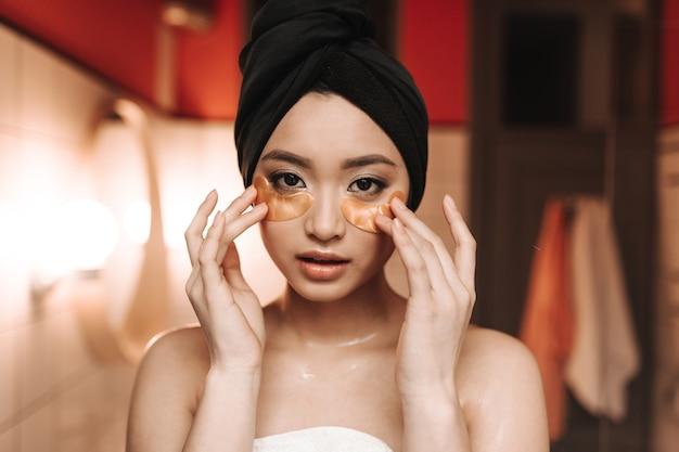 Mulher bonita olhando para a frente e colocando adesivos hidratantes sob os olhos