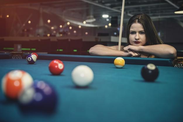Mulher bonita olhando para as bolas de bilhar na mesa