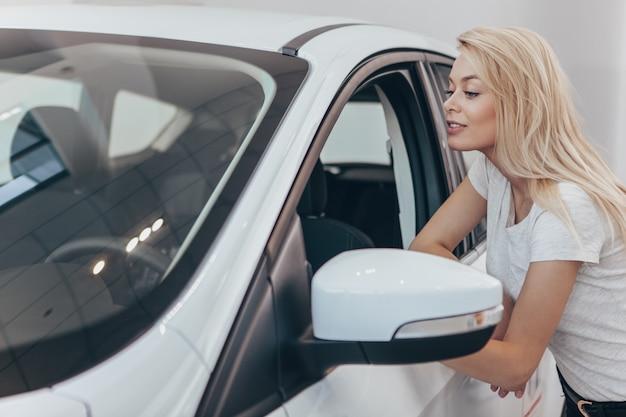 Mulher bonita, olhando para dentro de um carro novo no espaço da cópia do salão de concessionária