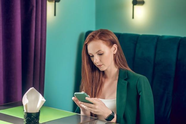 Mulher bonita olhando para smartphone em um café