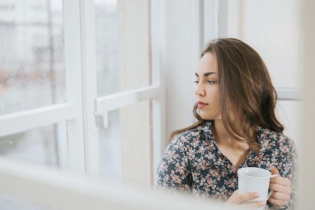 Mulher bonita olhando pela janela em dia chuvoso.