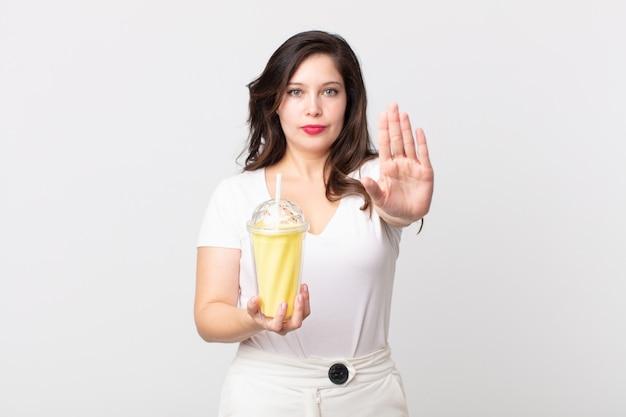 Mulher bonita olhando séria, mostrando a palma da mão aberta fazendo gesto de pare e segurando um milkshake de baunilha