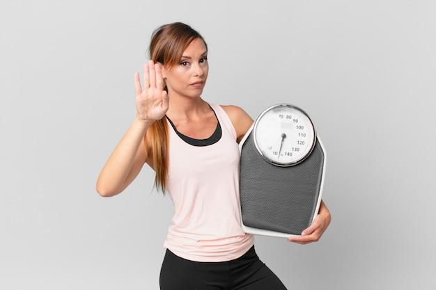 Mulher bonita olhando sério mostrando a palma da mão aberta, fazendo gesto de parada. conceito de dieta