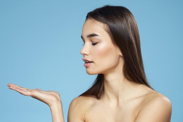 Mulher bonita ombros nus cabelo cuidados close-up banco fundo azul.