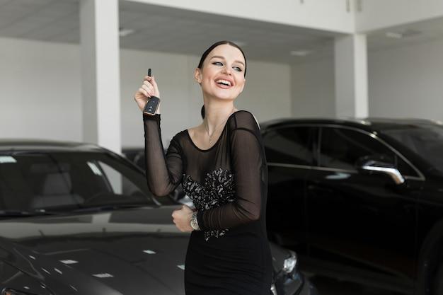 Mulher bonita ou vendedor de carros segurando a chave remota de um carro novo em um showroom