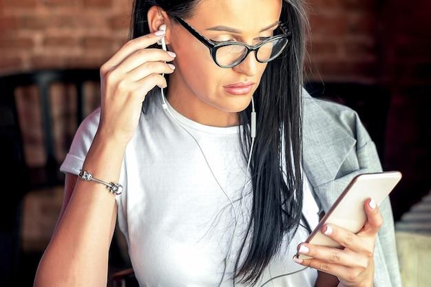 Mulher bonita ouve música com seu telefone inteligente em um café.