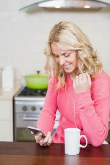 Mulher bonita ouvir música na cozinha