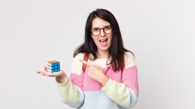 Mulher bonita parecendo animada e surpresa apontando para o lado e resolvendo um jogo de inteligência