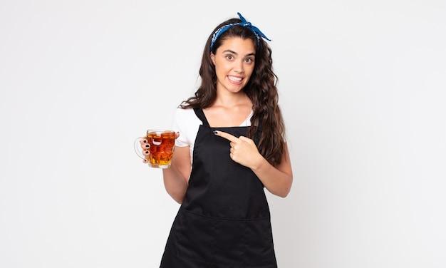 Mulher bonita parecendo animada e surpresa, apontando para o lado e segurando um copo de cerveja
