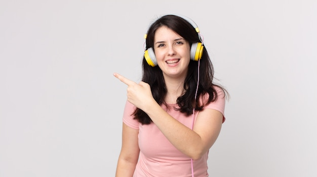 Mulher bonita parecendo animada e surpresa apontando para o lado ouvindo música com fones de ouvido