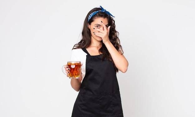 Mulher bonita parecendo chocada, assustada ou apavorada, cobrindo o rosto com a mão e segurando um copo de cerveja