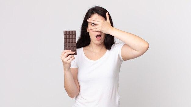Mulher bonita parecendo chocada, assustada ou apavorada, cobrindo o rosto com a mão e segurando uma barra de chocolate