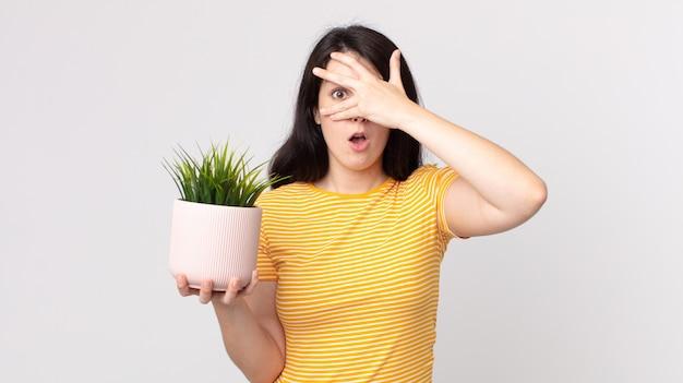 Mulher bonita parecendo chocada, assustada ou apavorada, cobrindo o rosto com a mão e segurando uma planta decorativa