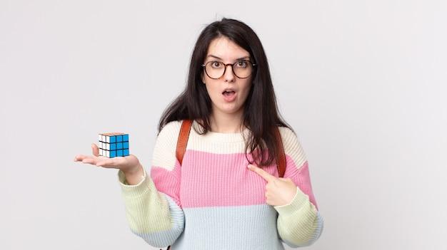 Mulher bonita parecendo chocada e surpresa com a boca bem aberta, apontando para si mesma e resolvendo um jogo de inteligência