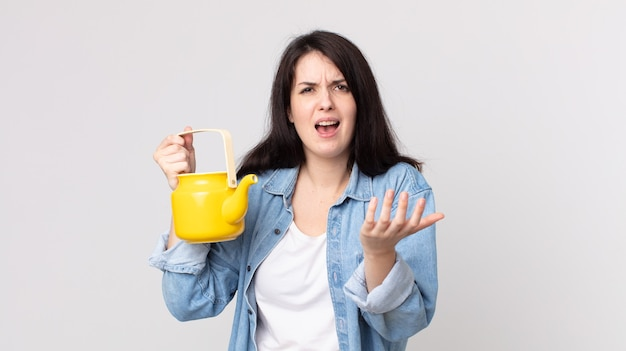 Mulher bonita parecendo desesperada, frustrada e estressada segurando um bule
