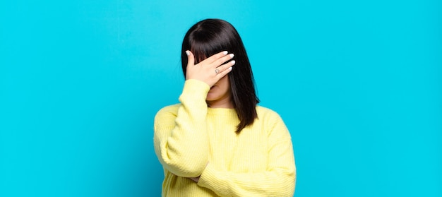 Mulher bonita parecendo estressada, envergonhada ou chateada, com dor de cabeça, cobrindo o rosto com a mão