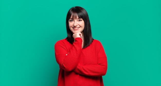 Mulher bonita parecendo feliz e sorrindo com a mão no queixo, pensando ou fazendo uma pergunta, comparando opções