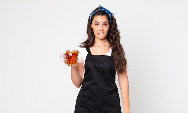 Mulher bonita parecendo perplexa e confusa segurando um copo de cerveja