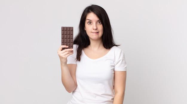 Mulher bonita parecendo perplexa e confusa segurando uma barra de chocolate