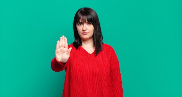 Mulher bonita parecendo séria, severa, descontente e irritada mostrando a palma da mão aberta fazendo gesto de pare