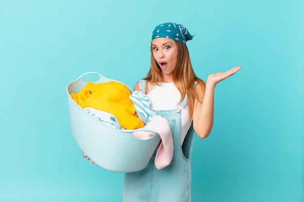 Mulher bonita parecendo surpresa e chocada, com o queixo caído segurando um objeto segurando uma cesta de lavagem