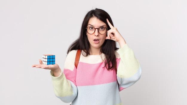 Mulher bonita parecendo surpresa, percebendo um novo pensamento, ideia ou conceito e resolvendo um jogo de inteligência
