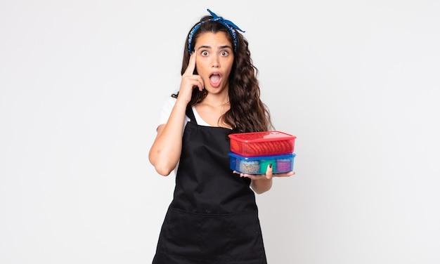 Mulher bonita parecendo surpresa, percebendo um novo pensamento, ideia ou conceito e segurando tupperwares com comida