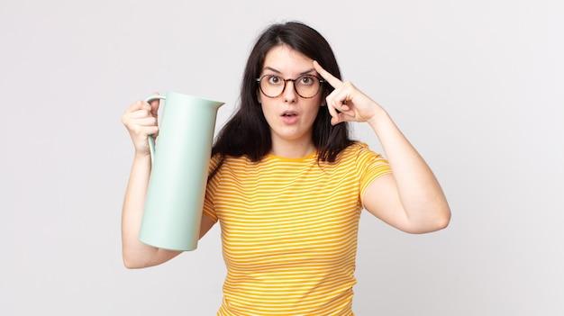 Mulher bonita parecendo surpresa, percebendo um novo pensamento, ideia ou conceito e segurando uma garrafa térmica de café